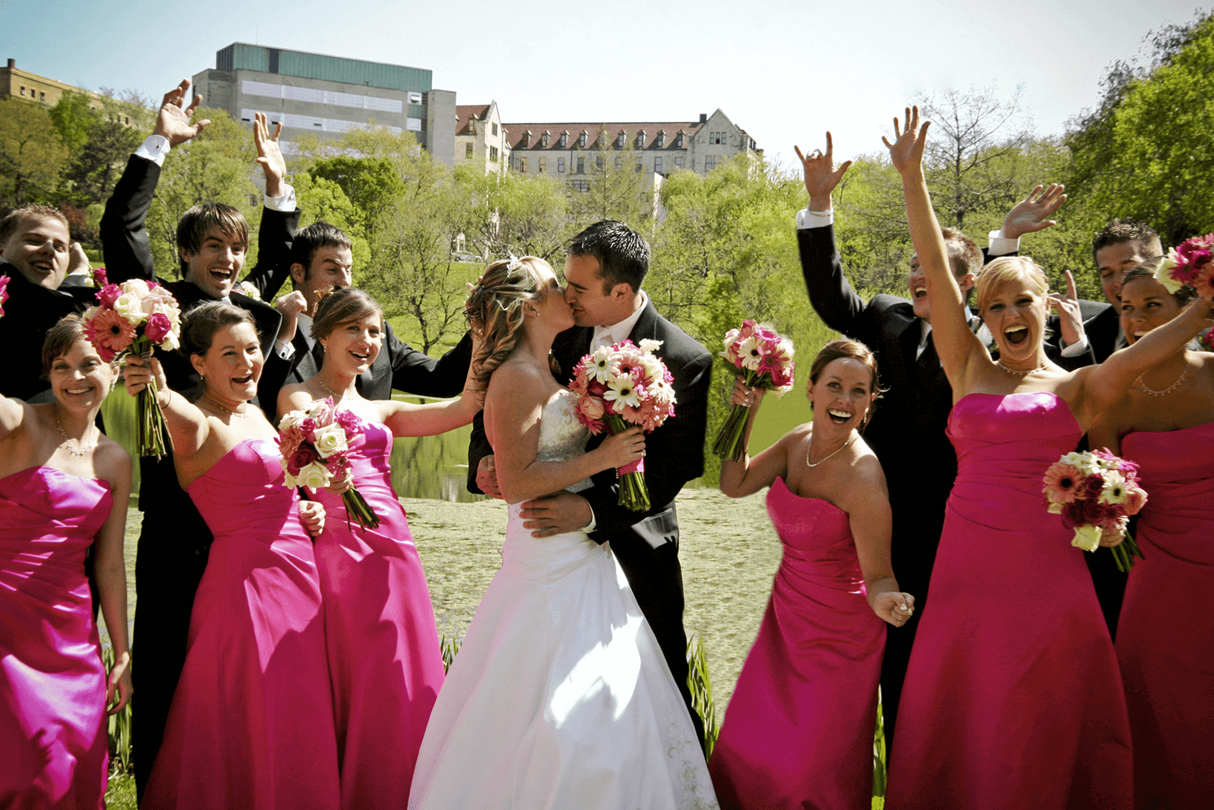 Bride and Groom Kissing Surrounded by Bridal Party