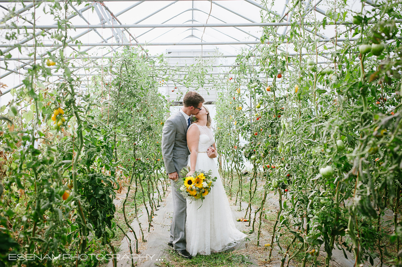 Bride and Groom standing in a green house of greenery